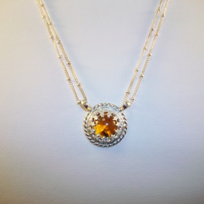 Round citrine cabochon bezel set in sterling silver with double chain.